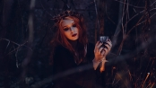 A beautiful witch holds a cup of wine in the dark woods