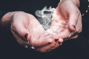 Hands cupping magic smoke.
