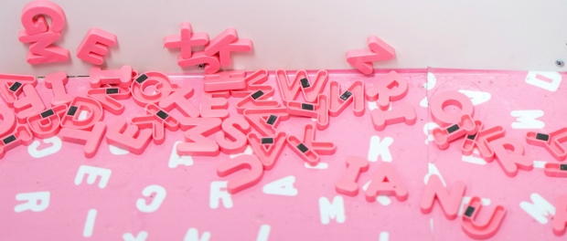 pink letters fall from the fridge to the floor