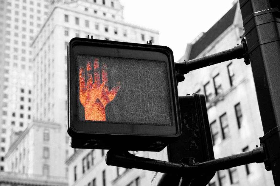 Red hand on city crosswalk sign